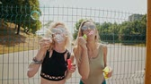 女らしさ : Cheerful hipster girls in sunglasses having fun making bubbles outdoors