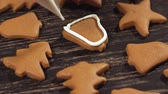 biscoitos : Close up garnishing homemade gingerbread bell. Decoration of Christmas cookies. Stock Footage