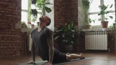 пилатес : Young man practicing yoga indoors. Guy doing an asana on black mat indoors in slow motion