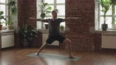 пилатес : Young sporty man doing warrior yoga pose in studio with wooden floor and big windows. Freedom, health and yoga concept in slow motion. Guy in shorts