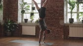 пилатес : Young man doing hand standing pose. Guy doing yoga indoors near windows. Yogi master workout on black mat in studio. Guy doing yoga indoors near windows. Healthy lifestyle concept with copy space