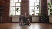 пилатес : Man practice yoga lotus pose in studio with brick wall and windows. Attractive man making yoga pose in gym Стоковые видеозаписи