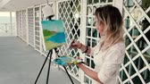 picture : Female artist painting a seascape outdoors