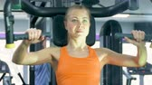 drilling machine : Athletic young woman working out on a fitness exercise equipment at the gym. Health, sport and workout concept - 4K stock footage video
