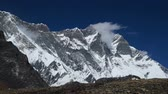 passar : Movement of clouds near a huge rocky mountain in the Himalayas. Time lapse, zoom out. Nepal