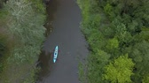 Aerial view of kayak floats along a calm river among the trees