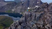 Aerial - Flying around tourists on peak of a high mountain. Lafoten islands. Norway 4k Stock Footage