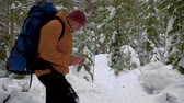 bússola : A man with a backpack travels in the winter forest. Tourist is guided by a compass. Beautiful view of the winter forest. 4K