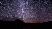 trilhas : Time lapse of Star trails in the night sky over mountains. 4K