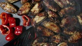 batatas fritas : The cook adds salt to the chicken wings and red pepper on the surface of a hot grill