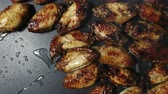 hálaadás : The cook adds salt to the chicken wings and red pepper on the surface of a hot grill
