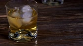 címke : Ice cubes melts in a glass of malt whiskey. Stock mozgókép