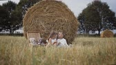 amoras : Bale of straw in the field. A little boy and girl get fruit. Picnic in the field.