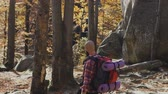 альпинист : A young man with a beard descends from the mountains. A tourist with a backpack on his shoulders. The traveler went on a hike in the forest in the autumn season Стоковые видеозаписи