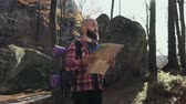 bald : Stylish hipster man traveler with backpack holding map and exploring on top of mountains, travel concept. Autumn. A handsoome man wearing a beard keeps a tourist map in his hands Stock Footage