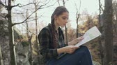 enciclopédia : Beautiful young girl with long hair braided in a braid, sitting on a rock in the woods and looking at the map. Golden autumn Stock Footage