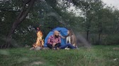 поход : Rest on camping - A man who has a beard and woman with long hair is sitting at the burning fire in a tent town Стоковые видеозаписи