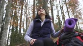 long distance : Close-up. Person hiking - woman hiker with backpack sits in forest resting during hike in beautiful forest, autumn tourism concept