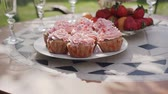 Close-up. Sweet round cakes in pink with strawberries, grapes and tangerines on table. Happy wedding concept. Party sweets