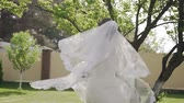Close-up. Beautiful bride in fantastic wedding dress with long lace spinning around and having walks in the spring garden near her house Dostupné videozáznamy