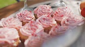 Close-up of sweet pastries in baskets with pink tasty cream set on a dessert plate that stands on the table