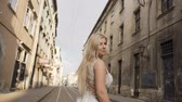 Beautiful young blonde girl in a white dress with long hair goes through the streets of the city in the morning. Sunrise, charming bride