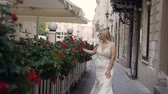 Sexy blonde in beautiful white long dress with long hair goes down streets old city and hand touches the red flowers that are in the vases. Warm summer morning, sunrise