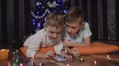 esparso : Close plan - two little brothers lie on ornate orange pillows on the floor in the living room near the Christmas tree and play online games on their gadget. Colored garlands