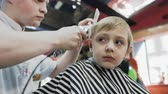 hair cut : The hairdresser doing a stylish haircut for a little boy in barbershop. The magic little boy make a new hairstyle in the mens hairdressing salon Stock Footage