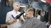 střih : Barber dries hair the little boy in hairdressing salon. Little beautiful boy getting haircut by barber while sitting In chair at barbershop