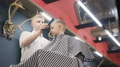 man grooming : Barber does hair styling to a small boy with the help of a comb and a hairdryer in a hairdressing salon, barbershop Stock Footage
