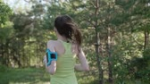 but : Rear view. Runner young woman running in park exercising outdoors fitness tracker wearable technology. Athletic girl training outdoor in the park