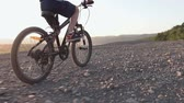 behind the wheel : Rear view of a black mountain bike on which the guy rides for a walk 8-9 years. A child who rides a bicycle in the hills area at sunset in summer Stock Footage