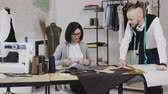 needlewoman : Team work of two tailor and dressmaker who are smile and working on sewing a new collection. The seamstress cuts pattern with scissors and the stylist follows the workflow Stock Footage