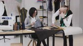 blondehair : Team work of two tailor and dressmaker who are smile and working on sewing a new collection. The seamstress carved a pattern with a gray fabric and the stylist follows her the workflow Stock Footage