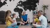 lad : Group of kids sitting on the floor in circle around the teacher and studying geography in geography classroom. Cute little children with teacher in classroom at school