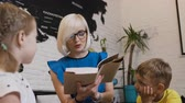 teach : Young blonde woman in eyeglasses read a book for children in the room against the background of the world map. Two pupils and teacher reading the book