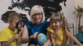 lad : Portrait of the lovely two pupils and young teacher in glasses with fun studying the globe with a dandruff in her hands in classroom. At the lesson of geography or history Stock Footage