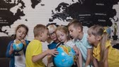 loupe : Close-up. An attractive teacher are educating five of his pupils at elementary school and using a globe to teach them about the world. Geography lesson. Boys, girls and their young teacher study the map of the world using the globe and magnifying glass