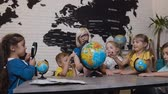 teach : Cute pupils and teacher looks at globes in geography classroom at the elementary school. Boys, girls and their young teacher study the map of the world using the globe and magnifying glass