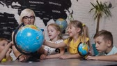 uczeń : Beautiful pupils and teacher looks at globes in geography classroom on the lesson at the elementary school. Boys, girls and their young teacher study the map of the world using the globe and magnifying glass