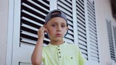 earbuds : Kid dressed in cap and t-shirt wearing white headphones is listening to good song from a smartphone isolated on white background. Portrait of a cute boy who listens to the good music Stock Footage