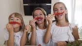 pimenta : Two sisters and their mother dressed in white clothes are having fun with chili pepper at home in the kitchen. Girls make mustache from red pepper chili and have fun looking at the camera Vídeos