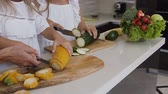 couve flor : The female hands cutting zucchini with a knife. Dark green and yellow zucchini laying on a cutting board in a kitchen. Two girls is cutting green and yellow zucchini on the board with knife at the kitchen table