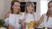 offspring : Cute little girl with her mom and older sister dressed in white clothes having fun makes a pyramid with zucchini at the kitchen table at home in the kitchen. Happy family, healthy food, vegetables