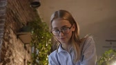 contador : Beautiful girl wearing glasses with long hair is working at evening time in modern office. Concentrated beautiful businesswoman making notes at table with laptop in office