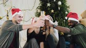 clinking : Happy young people drinking wine during celebrate New Year or Christmas Eve, having great time in relaxing home atmosphere near christmas tree Stock Footage