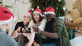papai noel : A group of people from different races posing and taking pictures on the phone. Cheerful friends in Santa hats make a photo on the smartphone at the christmas celebrate, good-looking young people celebrating new year or christmas eve