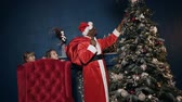 spying : Santa Claus putting toy on the christmas tree while two girls spying for him. Stock Footage