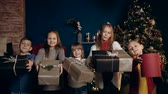 presentes : Beatiful five children laughing and moving present to the camera. Vídeos